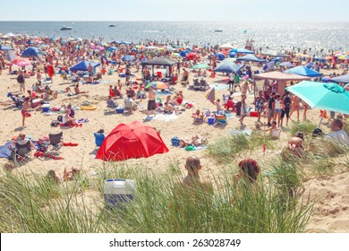 Beach scene on a busy summer day with blurred out people. Focus on grass in foreground