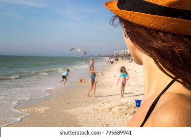 Beach scene- Pretty beach woman detail watching children playing on sun in swimwear at beautiful sea sandy beach, Sunny Sunday family relax and leisure on ideal warm day, Mexican Gulf coast Florida