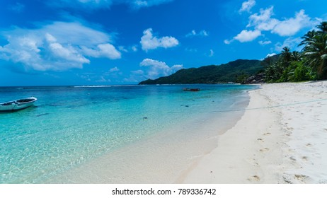 Beach scene in Seychelles.  Light clouds with deep blue sky, blue Indian Ocean and white sandy beach.