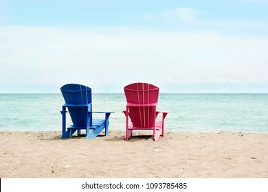 Beach scene with two empty Muskoka chairs in blue and pink color at Kew-Balmy Beach in Toronto facing Lake Ontario.
