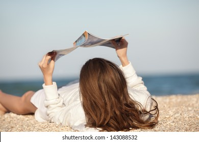 Beach scene. Young woman reading magazine
