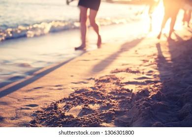 beach scenery in sunset/ peaple are walking on the beach on sunset