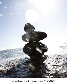 Beach sculpture from a stone of the beautiful girl in water splashes.