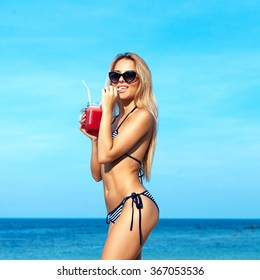Beach sea blue sky summer vacation portrait of pretty blonde young woman having fun and smiling on the beach in bikini with red cocktail