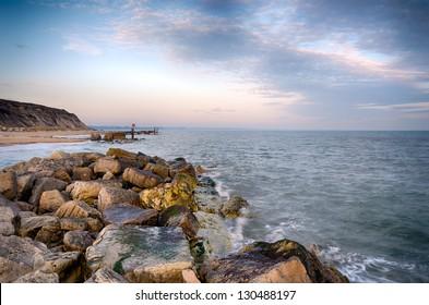 The beach and sea groynes at Hengistbury Head near Christchurch in Dorset under a Mackerel Sky