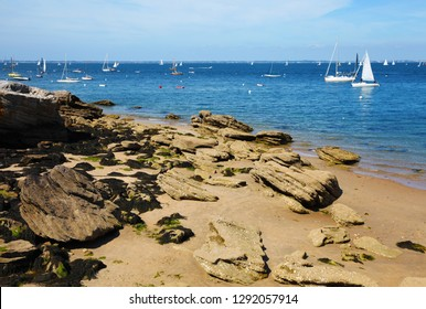 Beach and sea from the Noirmoutier-island, Vendee, France. Boats, buoys, sand, rock, seaweed and beach in Atlantic ocean.