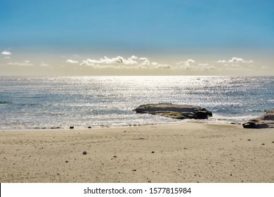 Beach section with quiet silver Atlantic Ocean in backlight with a large lava stone at the water's edge on the Canary Island of Tenerife.  Small white clouds with a light blue sky.