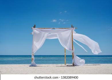 Beach shade with white gracefully fluttering fabric curtains on seashore. Sea breeze and white sand
