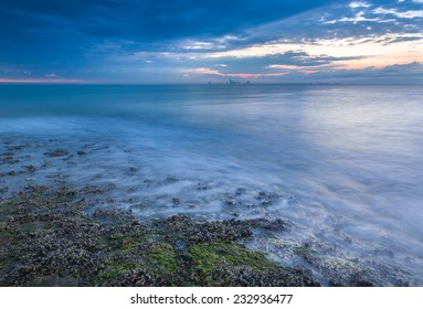 Beach shore at sunrise with view on a distant city