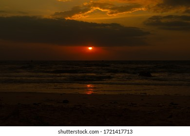 A beach shore wit the red sun shining in the background at Bình Hưng