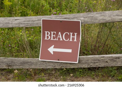 Beach sign on an old rusty wooden fence
