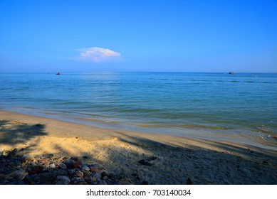 The beach and smooth blue sea with blue sky background