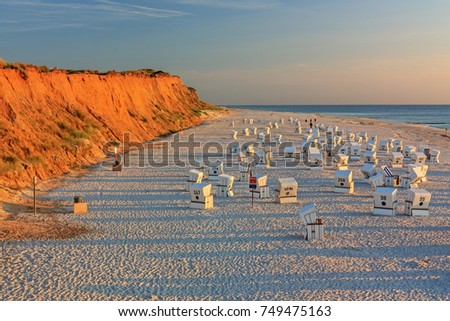 Beach with strandkorbs (beach basket chairs) at the Red Cliff(Rotes Kliff) at sunset near Kampen on Sylt at the North Sea, Schleswig-Holstein, Germany.
