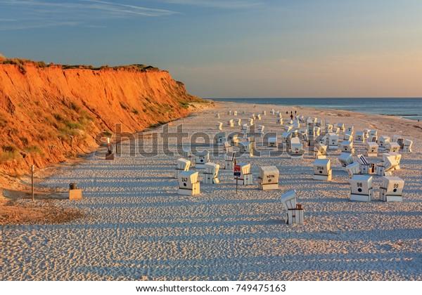 Strand mit Strandkorbs (Strandkorbstühle) an der Roten Klippe (Rotes Kliff) bei Sonnenuntergang in der Nähe von Kampen in Sylt an der Nordsee, Schleswig-Holstein, Deutschland.