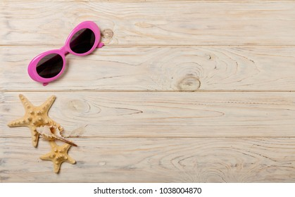 Beach summer concept. Female hat and pink sunglasses on a light wooden background. Selective focus.