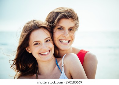 Beach in summer. A couple of young women in swimwear hugging affectionately in the sun on a summer day. Close-up photo of the smiling faces