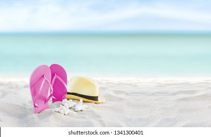 Beach summer holiday banner background. Flip flops and hat on sand near ocean. Summertime accessories on seaside. Tropical vacation and relax travel concept. Top view and copy space. Selective focus