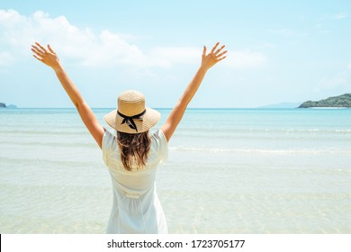 Beach summer holidays woman in happy freedom concept with arms raised. Woman wearing white dress and straw hat
