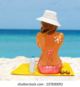Beach summer holidays. Woman wearing red bikini and beach hat sitting on the mat. Concept of sun protection, model with sunscreen and sunglasses.