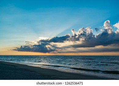 Beach, summer, relaxation and paysage concept- picturesque and beautiful sunset on the sea with sunrays and dark clouds above the north sea.