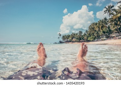 Beach summer vacation lifestyle background with foots in transparent sea palm trees as travel tropical lifestyle