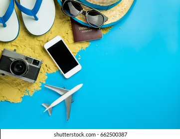 Beach Summer Vacation travel accessories and fashion on Sand and blue background.