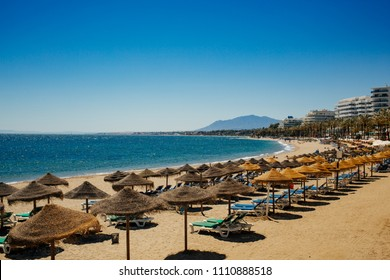 Beach with sun loungers in Marbella, Spain.