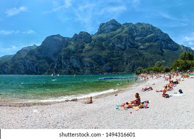 Beach with sunbathing people at lake in mountains, cliffs and blue sky in background, Lago di Garda, Riva del Garda, Italy