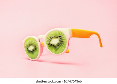 Beach sunglasses concept with kiwi on pink background