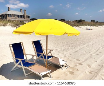 Beach and sunny yellow umbrella at the seashore.