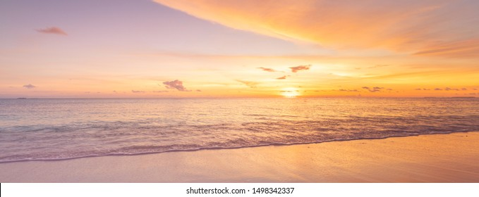 Beach sunset. Beautiful panoramic landscape, colorful golden sunset over calm sea with waves splashing softly on sandy beach. Amazing sunset landscape, summer nature, peaceful nature