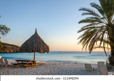 Beach sunset in Curacao a Caribbean Island. White beach, blue sky and crystal clear blue water. Sandy beach covered with million fragments of shells.