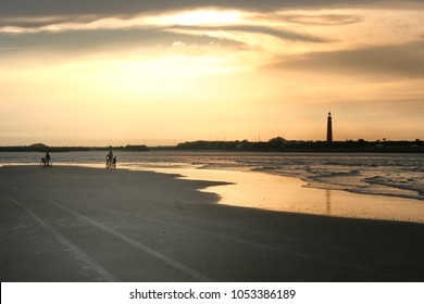 beach sunset with silhouettes on bikes and lighthouse in background