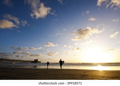 beach sunset with surfers and pier