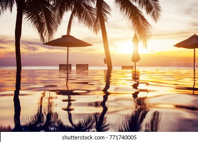 beach swimming pool at sunset with reflection of palm trees, tropical landscape, exotic island hotel
