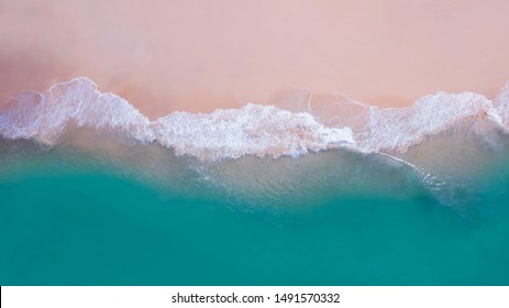 Beach top view or aerial view showing white wave foam hit the sand beach with turquoise water. Wave action, fluid dynamics.