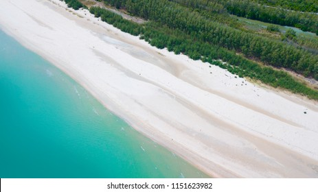 Beach top view or aerial view with turquoise water,white beach and green pine tree along the beach in Talumphuk Cape, Nakhon Si Thammarat,Thailand