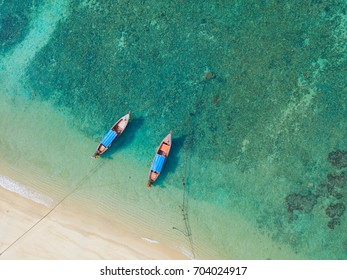 Beach top view or aerial view with two long tail boat on emerald water