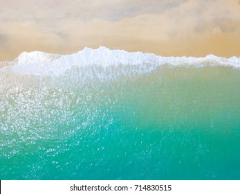 Beach top view with wave foam.Aerial view sandy beach and wave of emerald sea water.