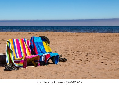 Beach towels and lounging chairs set up on sandy beach back dropped with blue ocean and sky.