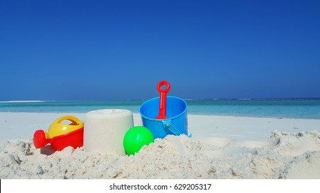 Beach toy bucket and space on the white sand with blue sea sky background