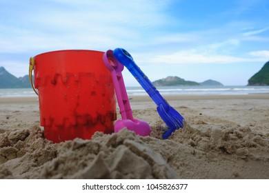 beach toys  buckets spade and shovel on sand, beach background
