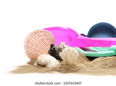 Beach toys for kids, plastic tools in sand pile with seashells isolated on white background