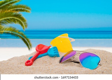 beach toys with sunglasses in background with idyllic tropical landscape