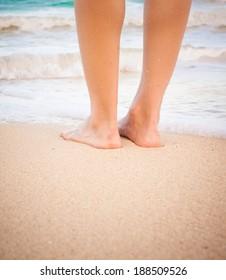 Beach travel - Closeup detail of female feet and golden sand on beach in Hawaii.