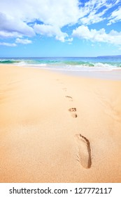Beach travel vacation concept - footsteps in sand on beautiful sunny summer day during getaway holidays under the blue sky. From Makena beach, Maui, Hawaii