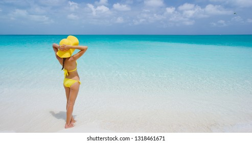 Beach Travel Vacation - Woman In Yellow Beach Hat And Bikini Relaxing On Beach. Turquoise sea and blue sky. Rear view of female wearing white sunhat and bikini. Tourist is enjoying vacation at beach.