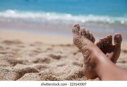 Beach travel - woman legs on sand beach. Travel concept. Vacation