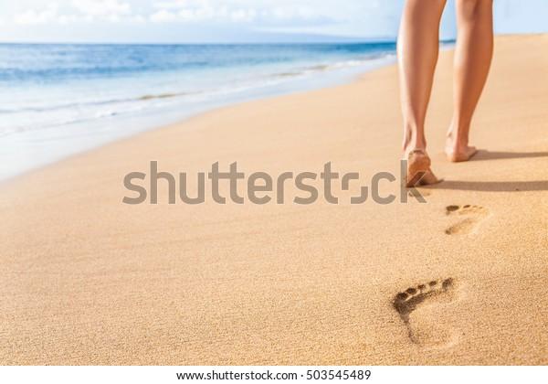 Podróż na plaży - kobieta relaksująca spacery po piaszczystej plaży pozostawiając ślady na piasku. Zbliżenie szczegóły kobiecych stóp i nóg na złotym piasku na plaży Kaanapali, Maui, Hawaje, USA.