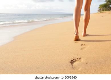 Beach travel - woman walking on sand beach leaving footprints in the sand. Closeup detail of female feet and golden sand on Kaanapali beach, Maui, Hawaii, USA.